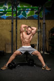 一个男性的画象与屈曲的在健身房背景干涉 有一个完善的身体的一个爱好健美者 执行健身他的人反映培训水 免版税图库摄影