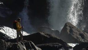 一个男性远足者观看在慢动作的巨大的瀑布 影视素材