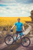 一个男性骑自行车者在一个美丽如画的黄色油菜籽领域乘坐 免版税图库摄影