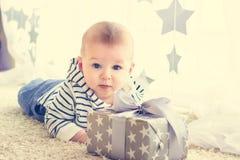 一个男婴的画象在他的礼物前面的在箱子 图库摄影