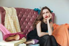 一个疲乏的被用尽的女孩的画象礼服的坐沙发 免版税库存图片