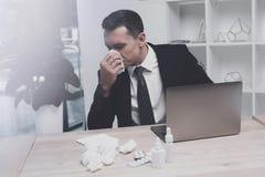 一个病的人在他的工作场所坐在办公室 他吹他的鼻子入一张纸巾 免版税库存图片