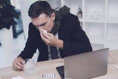 一个病的人在他的工作场所坐在办公室 他吹他的鼻子入餐巾 免版税库存照片