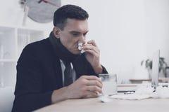 一个病的人在他的工作场所坐在办公室 他吹他的鼻子入餐巾 库存图片