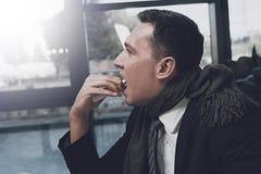 一个病的人在他的工作场所坐在办公室 他在一朵医疗浪花的喉头喷洒自己 免版税库存图片