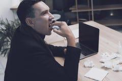 一个病的人在他的工作场所坐在办公室 他在一朵医疗浪花的喉头喷洒自己 免版税库存照片