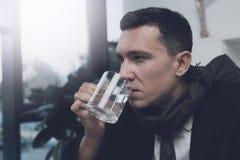 一个病的人在他的工作场所坐在办公室 他在他的手上拿着一杯水 免版税库存图片