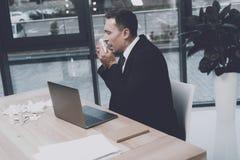 一个病的人在他的工作场所坐在办公室 他打喷嚏 库存照片