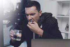 一个病的人在他的工作场所坐在办公室 他有一个药片和一杯水在他的手 库存照片