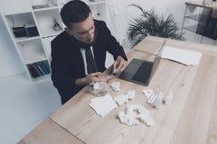 一个病的人在他的工作场所坐在办公室 他有一个药片和一杯水在他的手 免版税图库摄影