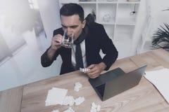 一个病的人在他的工作场所坐在办公室 他有一个药片和一杯水在他的手 免版税库存照片