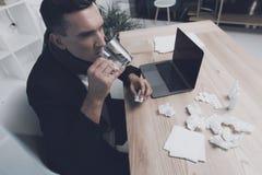 一个病的人在他的工作场所坐在办公室 他有一个药片和一杯水在他的手 免版税库存图片