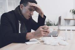 一个病的人在他的工作场所坐在办公室 他紧贴到他的头 免版税库存照片