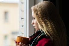 一个病的十几岁的女孩的画象有一个杯子的热的饮料 免版税库存图片