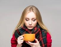 一个病的十几岁的女孩的画象有一个杯子的热的饮料 库存照片