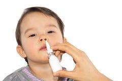 一个病的小女孩的父母的手应用被隔绝的鼻孔喷射 库存图片