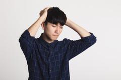 一个痛苦的亚洲青年时期的演播室画象,在他的手上拿着他的头 库存照片