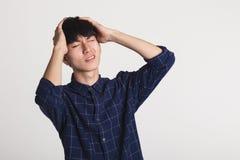 一个痛苦的亚洲青年时期的演播室画象,在他的手上拿着他的头 免版税图库摄影
