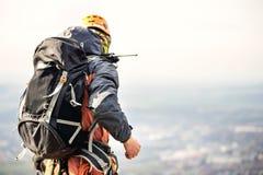 一个登山人的特写镜头从后面的在齿轮和有一个背包的用在传送带的设备,在一个岩石的立场,在上流 免版税图库摄影
