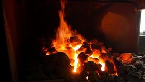 一个白炽熔炉在有煤炭的铁匠铺谎言炽热金属零件,细节的热治疗,伪造 影视素材