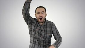 一个白种人人跑和呼吁某人,设法得到某人的在梯度背景的attantion 免版税库存图片