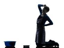 妇女佣人家事疲倦了腰疼洗涤的地板剪影 免版税库存照片