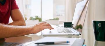 一个白种人男性的无首的庄稼使用他的膝上型计算机的 免版税图库摄影