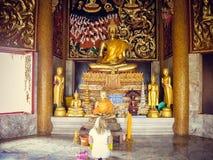 一个白肤金发的女孩在一个雕象前面下跪在泰国 免版税库存照片