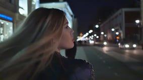 一个白肤金发的女孩在夜城市附近走 射击从后面和头发接近  影视素材