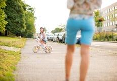 一个白肤金发的女孩坐她的自行车在城市公园附近 库存图片