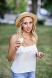 一个白肤金发的女孩的室外画象帽子的 庭院背景的少妇 一个女孩用柠檬 健康生活方式 库存图片
