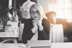一个白肤金发的女性商务伙伴的画象她的坐在她在她的计算机前面的整洁的书桌的30 `的s 免版税库存照片
