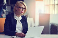一个白肤金发的女性商务伙伴的画象她的坐在她在她的计算机前面的整洁的书桌的30 `的s 免版税库存图片