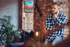 一个白肤金发的有胡子的行家男性在穿戴了牛仔裤和羊毛衬衣 免版税图库摄影