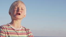 一个白肤金发的男孩的特写镜头反对天空蔚蓝的 股票录像