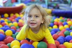 一个白肤金发的男孩的画象一件黄色T恤杉的 儿童微笑和戏剧在儿童的游戏室 球水池 免版税库存照片