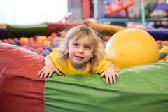 一个白肤金发的男孩的画象一件黄色T恤杉的 儿童微笑和戏剧在儿童的游戏室 球水池 库存照片