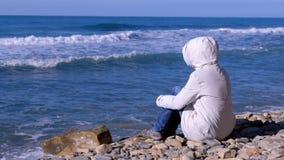 一个白色下来夹克和敞篷的妇女坐岸和神色在打反对石头的风雨如磐的海波浪 股票录像