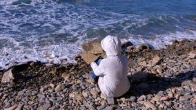 一个白色下来夹克和敞篷的妇女坐岸和神色在打反对石头的风雨如磐的海波浪 影视素材