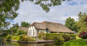 一个白色农厂房子的全景有茅屋顶的在羊角村 免版税库存照片