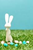 一个白色塑料兔宝宝小雕象显示用软心豆粒糖 图库摄影