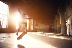 一个白色帽子和一件黑运动衫的一位年轻溜冰者在的一个被放弃的大厦做与冰鞋的一个把戏跳 免版税库存照片