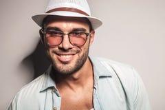 戴一个白色帽子和太阳镜的英俊的偶然人 免版税库存照片