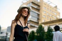 一个白色帽子和太阳镜的年轻美丽的妇女在街道上在城市在晚上在夏天 库存照片