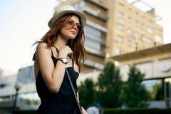 一个白色帽子和太阳镜的年轻美丽的妇女走沿一条街道的在城市 库存照片