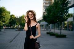 一个白色帽子和玻璃的年轻美丽的妇女走在夏天街道上的城市附近的 库存图片