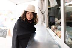 一个白色帽子的一个美丽的女孩在黑格子花呢披肩包裹了自己并且做在一个快餐吃饭的客人的命令 免版税图库摄影