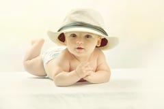 一个白色帽子的一个逗人喜爱的矮小的婴孩 免版税库存图片
