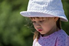 一个白色帽子的可爱宝贝女孩哀伤地降低了她的眼睛 库存照片