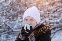 一个白色帽子的女孩有一杯茶的在积雪的树枝中的 免版税库存照片
